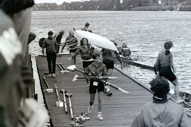 Women carrying boat on landing stage