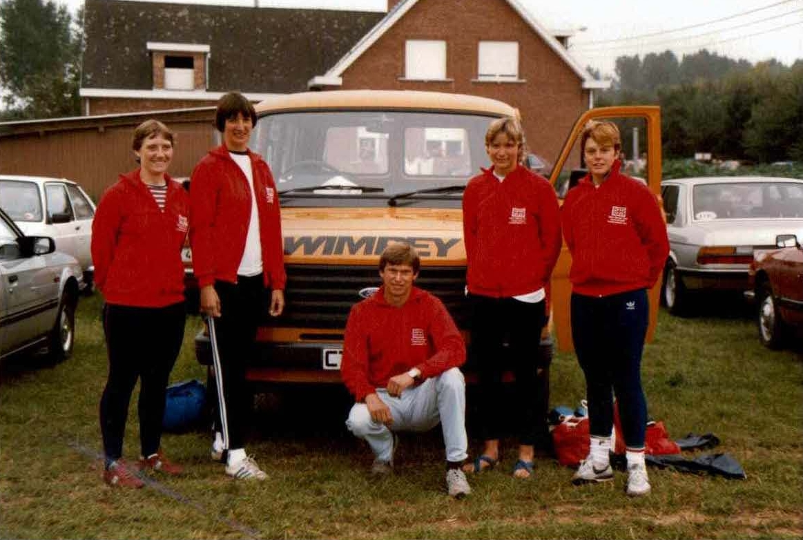 4 women and their coach by a yellow van with Wimpey om it