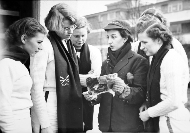 5 rowing women and cox looking at newspaper clipping
