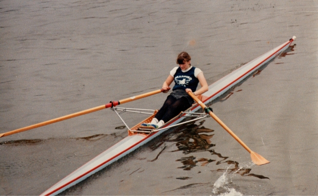 Young woman sculling in Bradford ARC vest