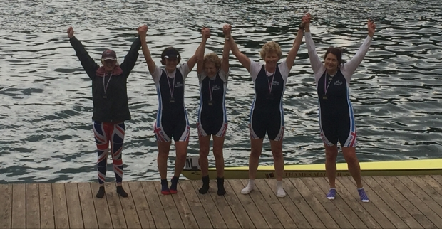 Women on medal raft with arms raised