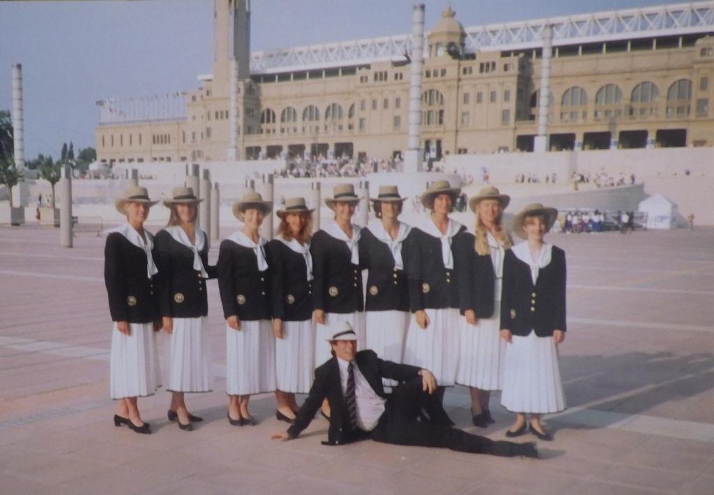 9 women in white skirts and navy blazers