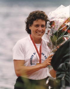 woman with medal and bouquet of flowers