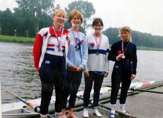 four women on raft with medals in assorted kit