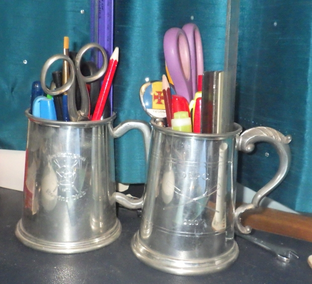 Pewter pots with pens and rulers in