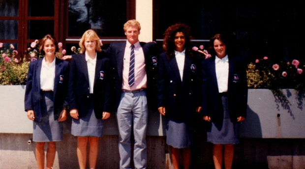 4 girls in blazers with male coach