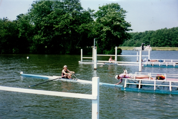 two women scullers on start with trees in background