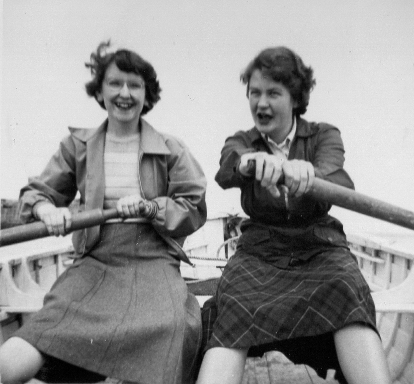 Two in skirts rowing in dinghy laughig