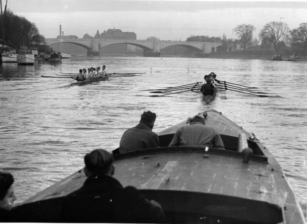 black and white photo of two women's eights followed by a launch containing 4 people