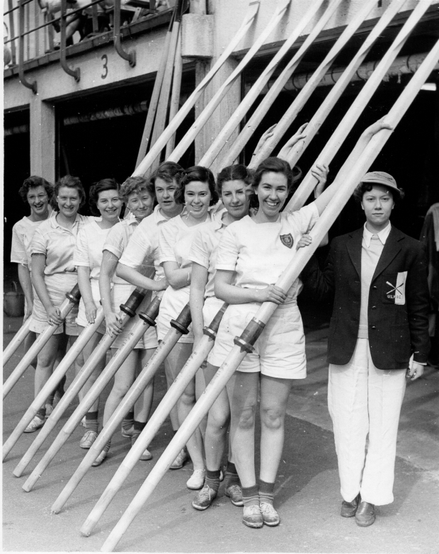 Women in front of boathouse with oars