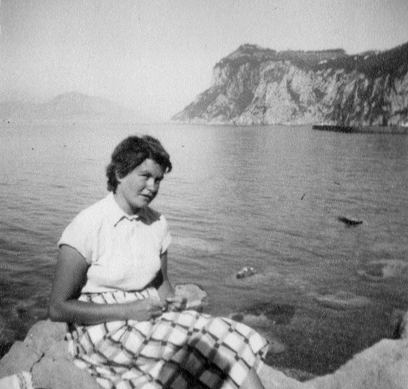 Woman sitting on rock by coastal bay