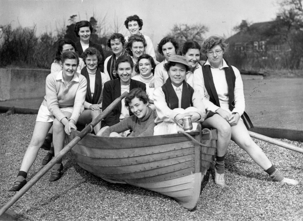 Women in rowing kit sitting in a dinghy on gravel