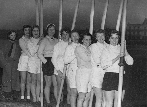 Eight women in shorts and white tops with oars vertical, cox in long coat and scarf