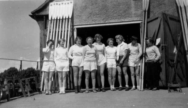 9 women with oars leaning up against boathouse
