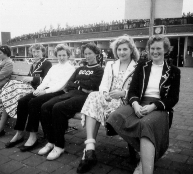 Five women sitting on bench - 3 in rowing blazers
