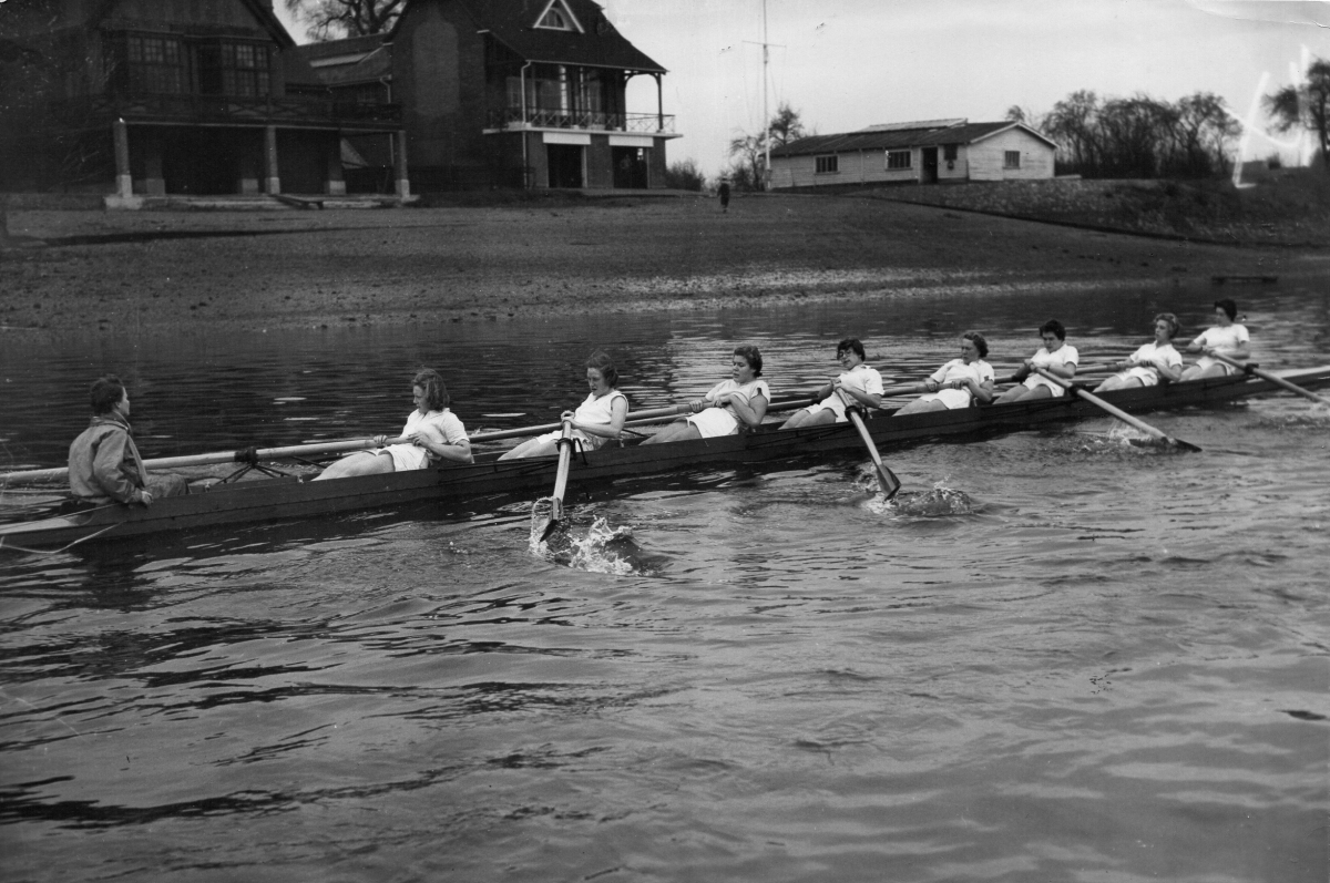 Women's eight leaning back at the finish passing Ibis and Quintin