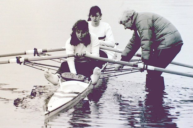 b/w photo of two women getting in double scull with male coach holding boat