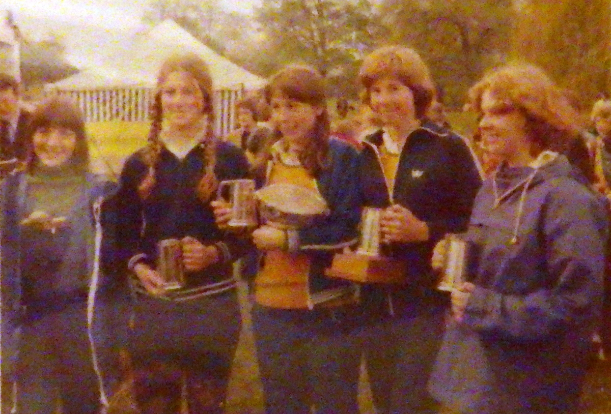 four girls with trophies and marquee in background
