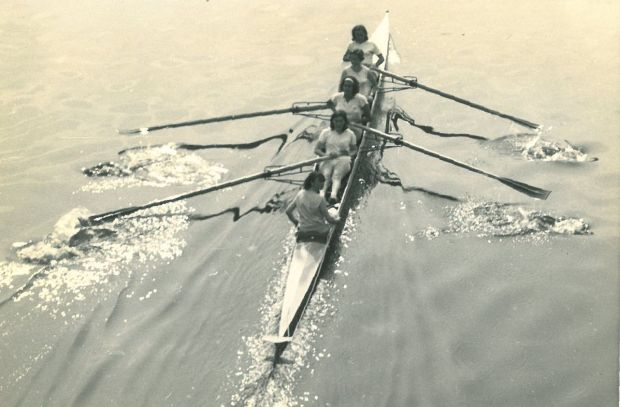 b/w photo of women's four on glasy water