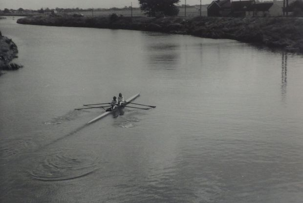 Two women in double scull at bend in river
