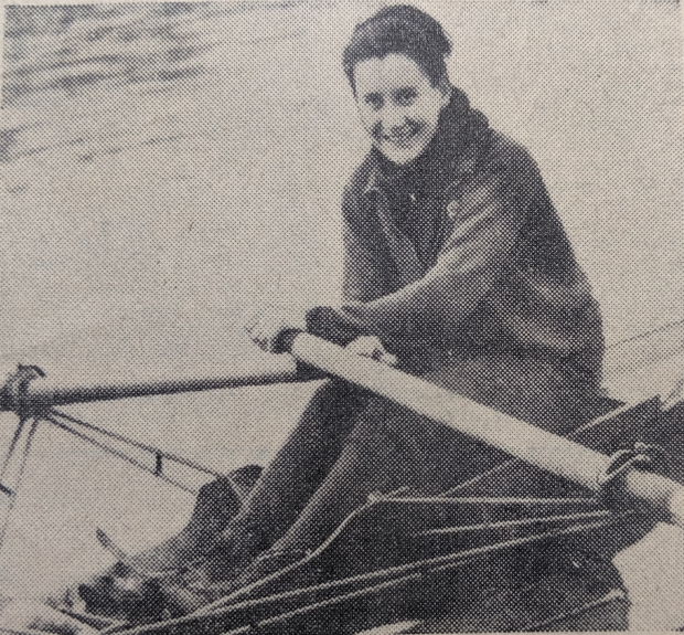 b/w photo of woman smiling in sculling boat