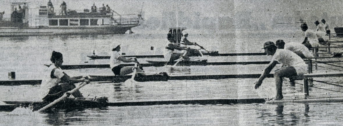 Black and white photo of 4 women starting sculling race