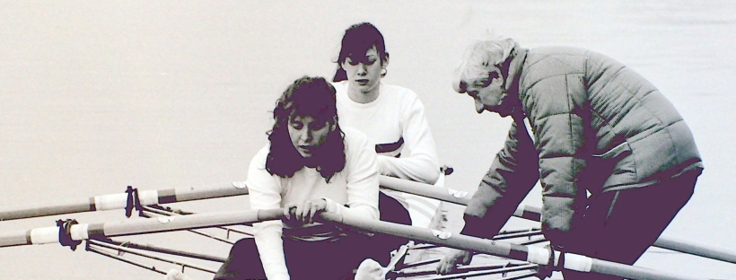 bw photo of 2 women boating in double scull with male coach