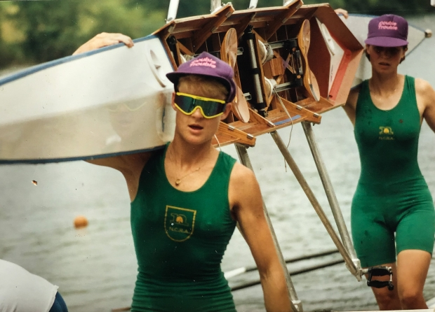 Two wome in green kit carrying boat