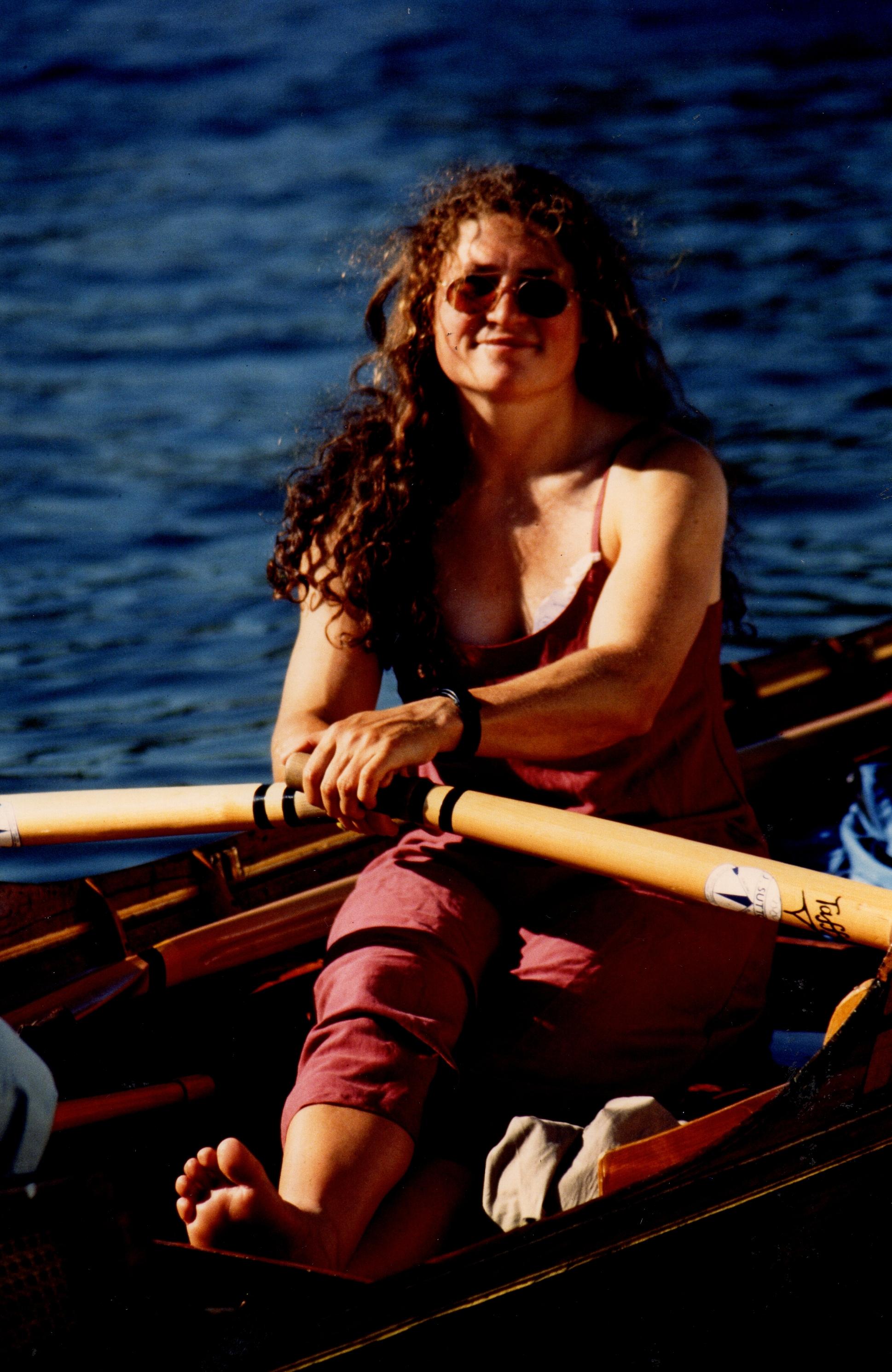 Woman in dress in skiff in sun