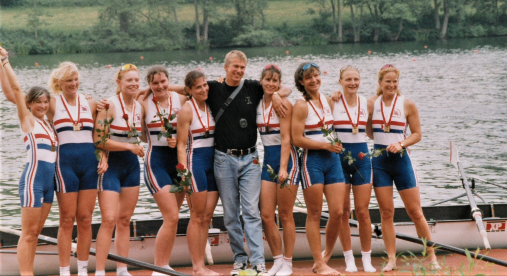 9 Happy women with coach on landing stage with red roses and medals