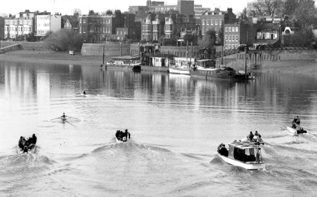 b/w photo of 2 scullers passing Dove Pier pursued by 5 launches