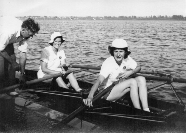 Two women wearing white hats in double scull on landing stage