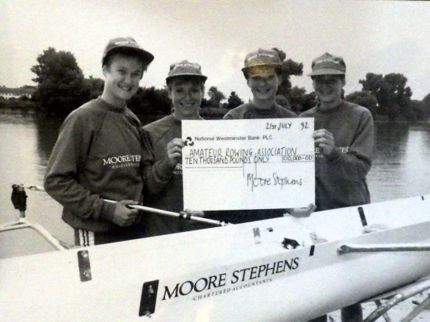 Women with cheque for £10,000 by boat with Moore Stephens on it