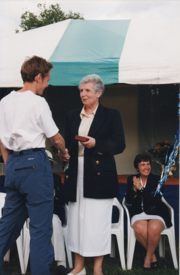 Woman in white top and blue trousers being given medal in red box