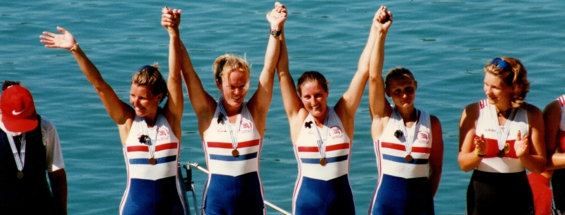 women's four with medals and arms aloft