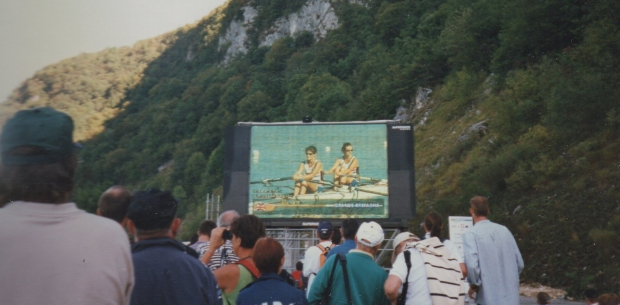 crowd with big screen showing racing