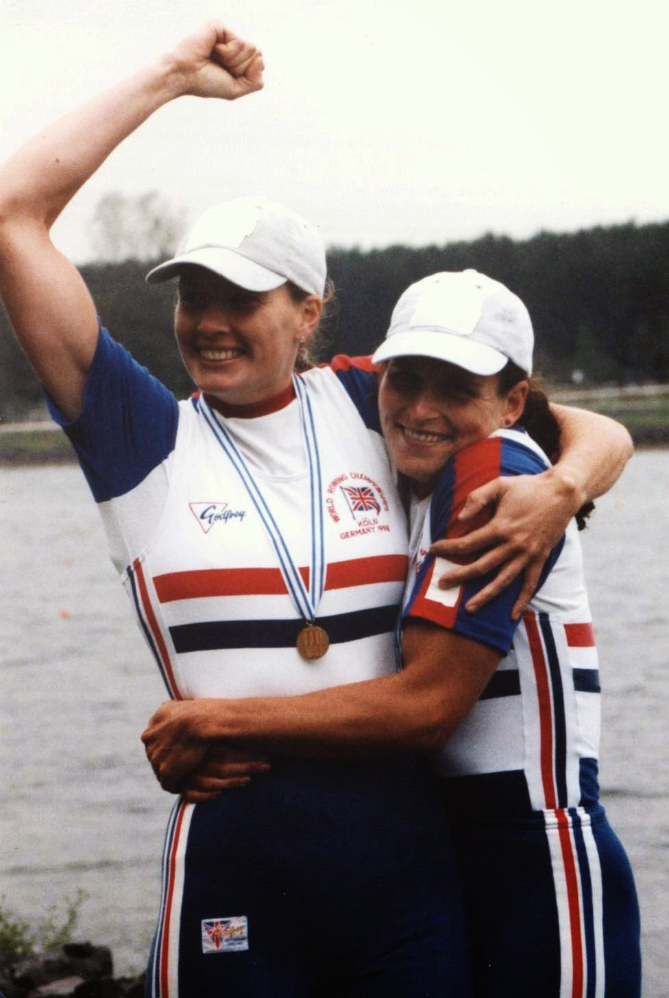 Two women hugging and looking happy with medals
