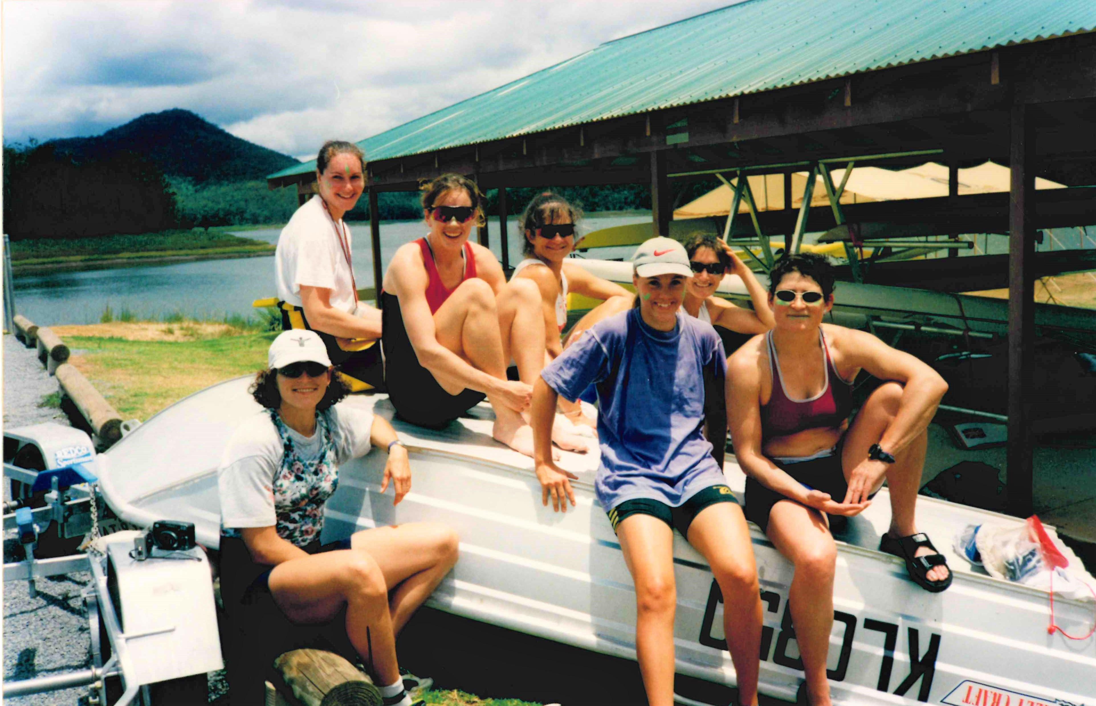 7 women sitting on upturned coaching launch by boat racks