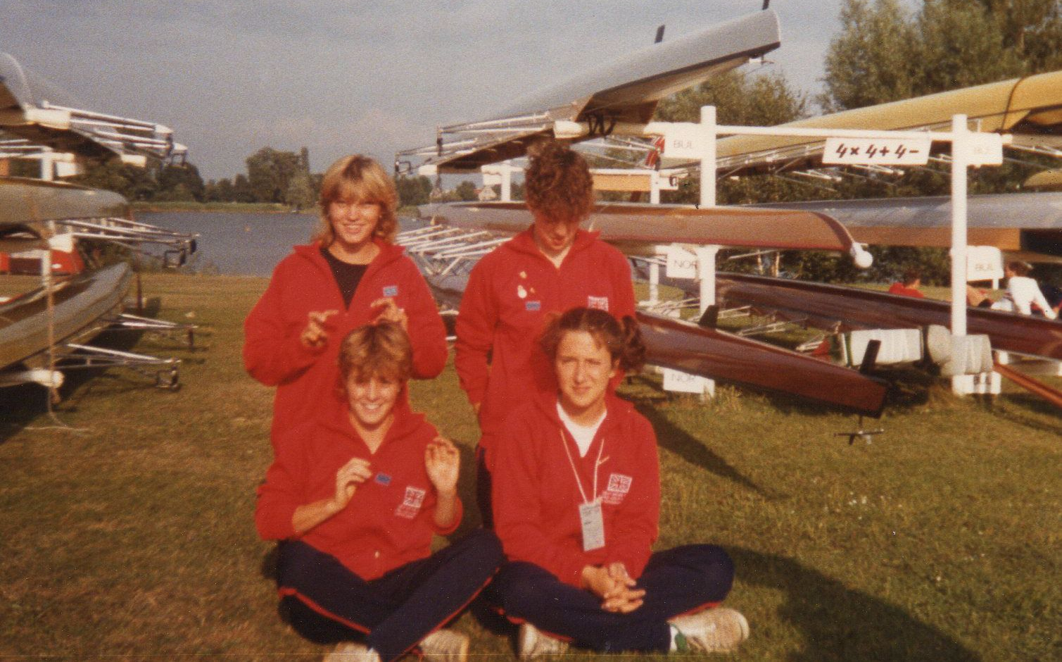 4 girls in red track suit tops by boat racks
