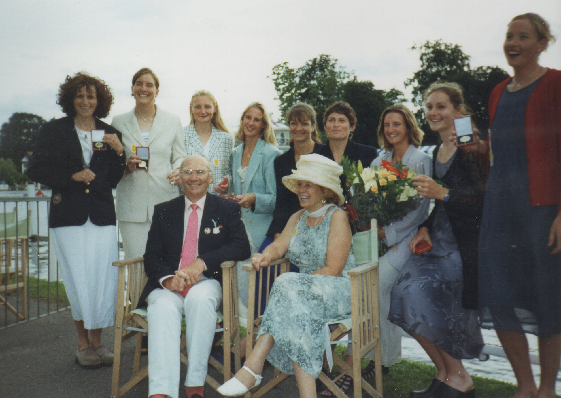 nine smiling women in dresses with medals and seated male coach and wife in hat