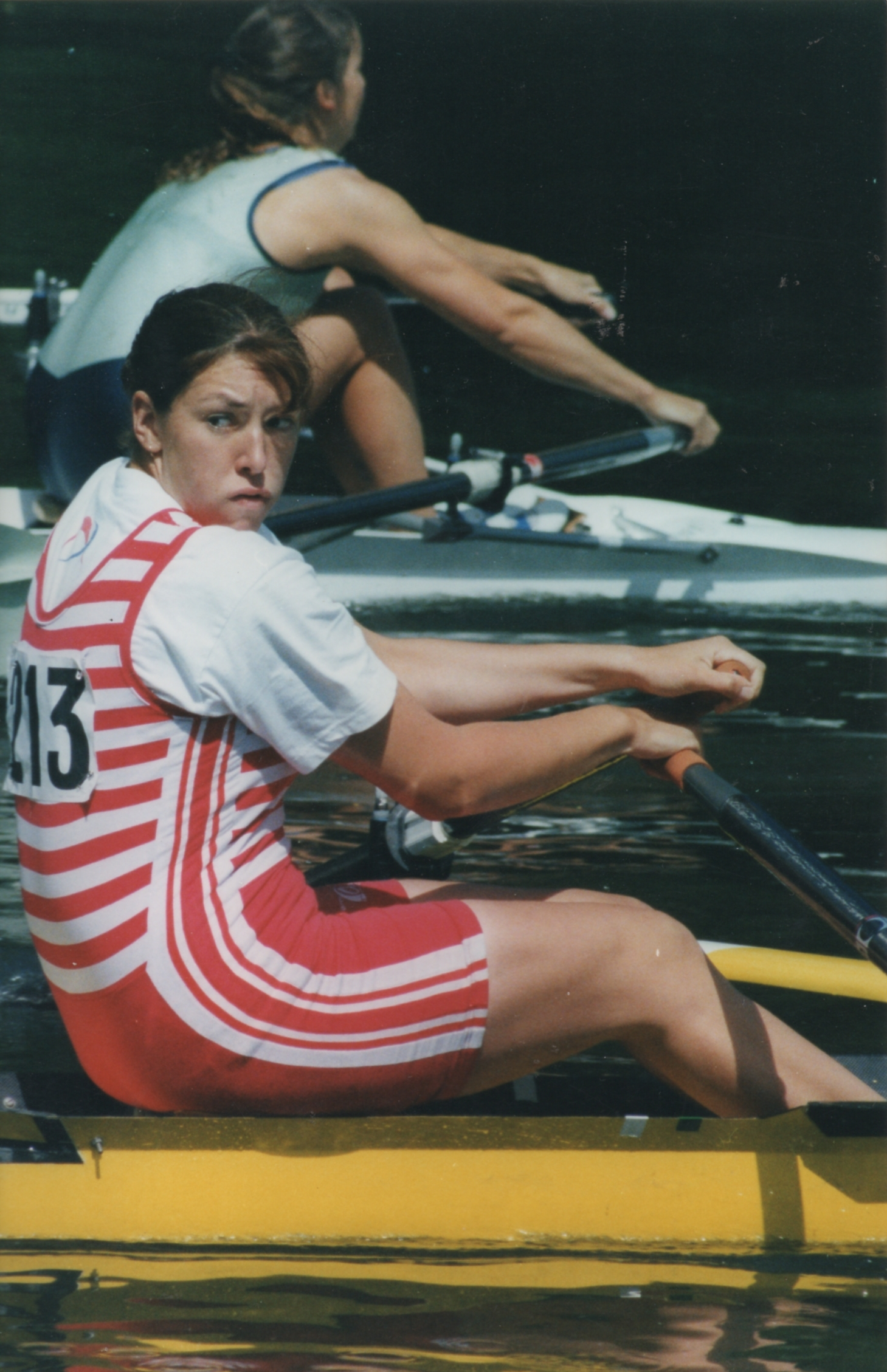 Woman in red and white striped Kingston RC kit just leading and looking round