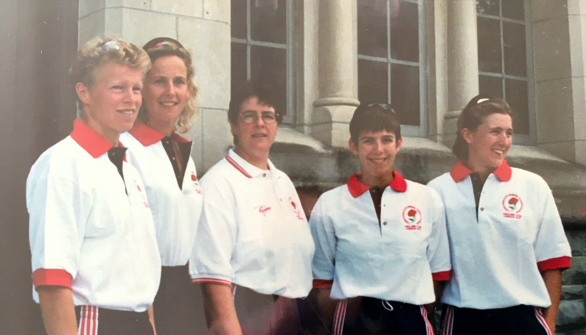 5 women wearing white polo shirts with England red roses on