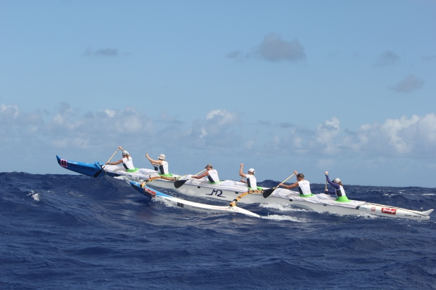 6 women in outrigger boat approaching top of a wave