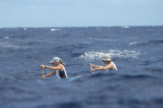 front 2 women in outrigger boat disappearing bhind a wave