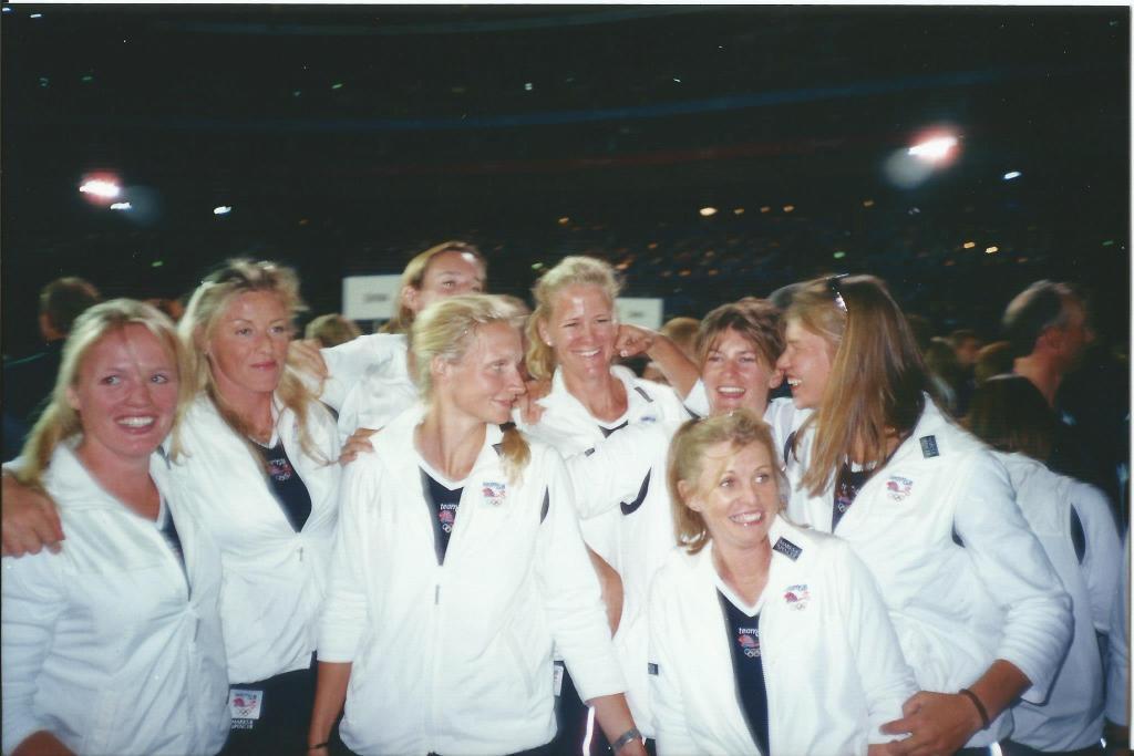 Women in white tracksuit tops in dark stadium