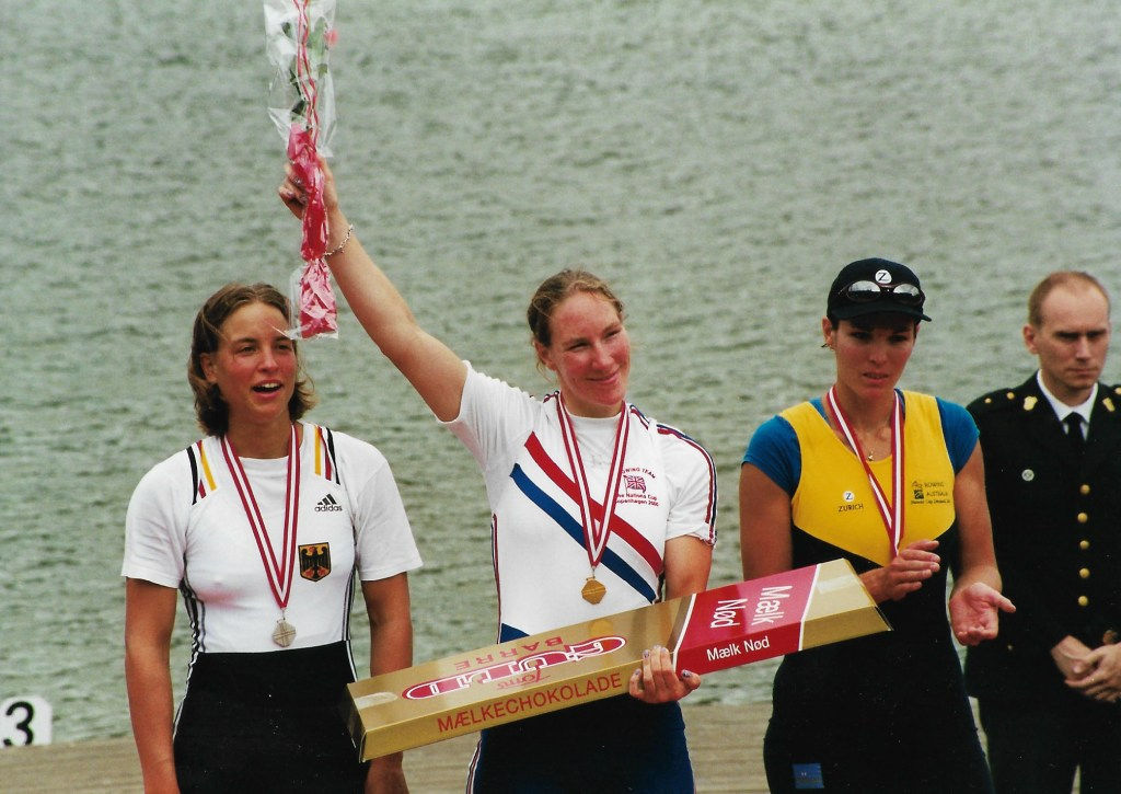 Woman in GBR kit holding bouquet and wearing gold medal