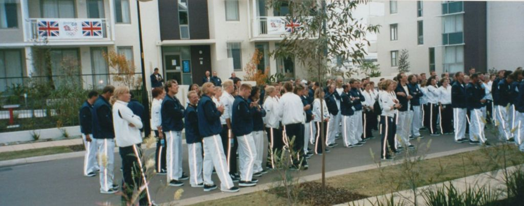 Group of athletes in blue and white tracksuits with reflective stripes on trousers