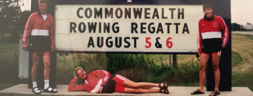 3 woen by sign saying Commonwealth Rowing Regatta, August 5 & 6