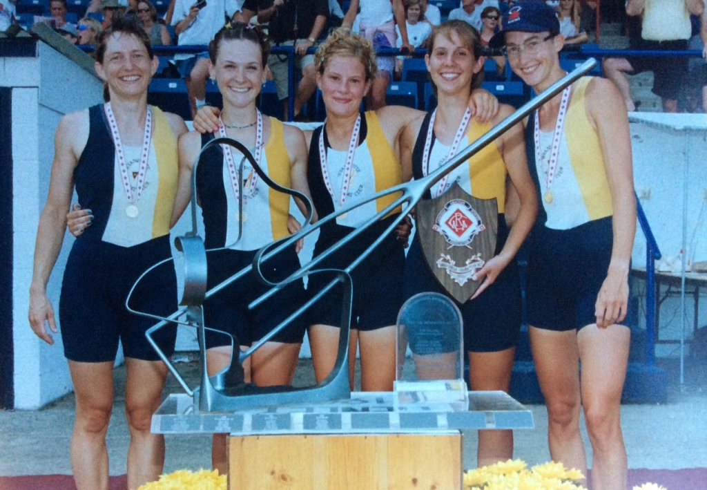 5 women with medals and oar-shaped trophy