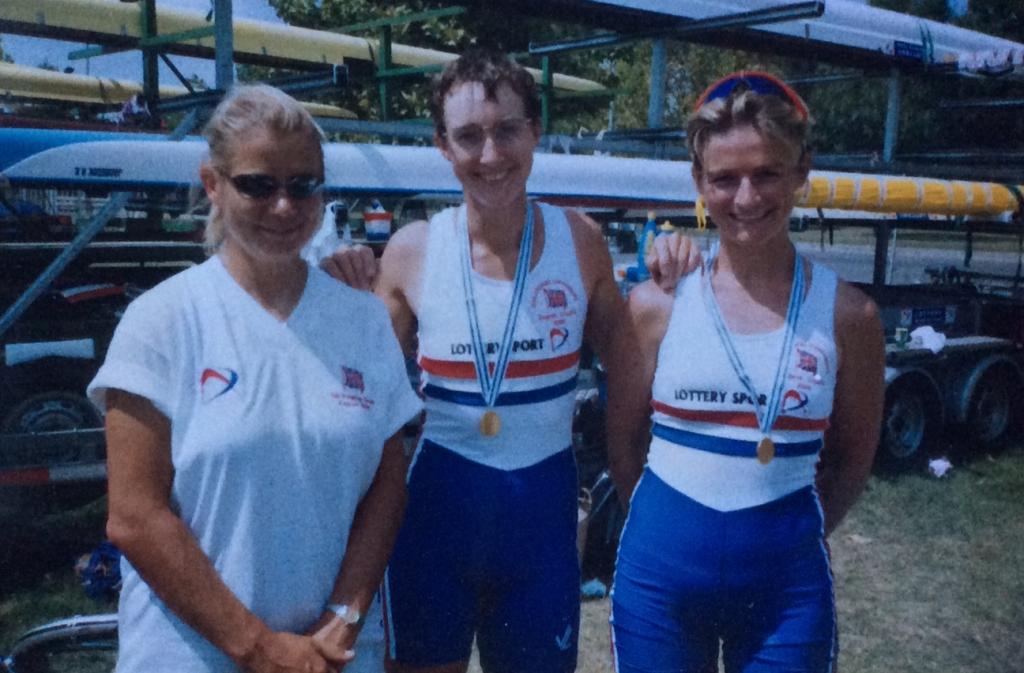 3women by boat trailer, 2 with medals
